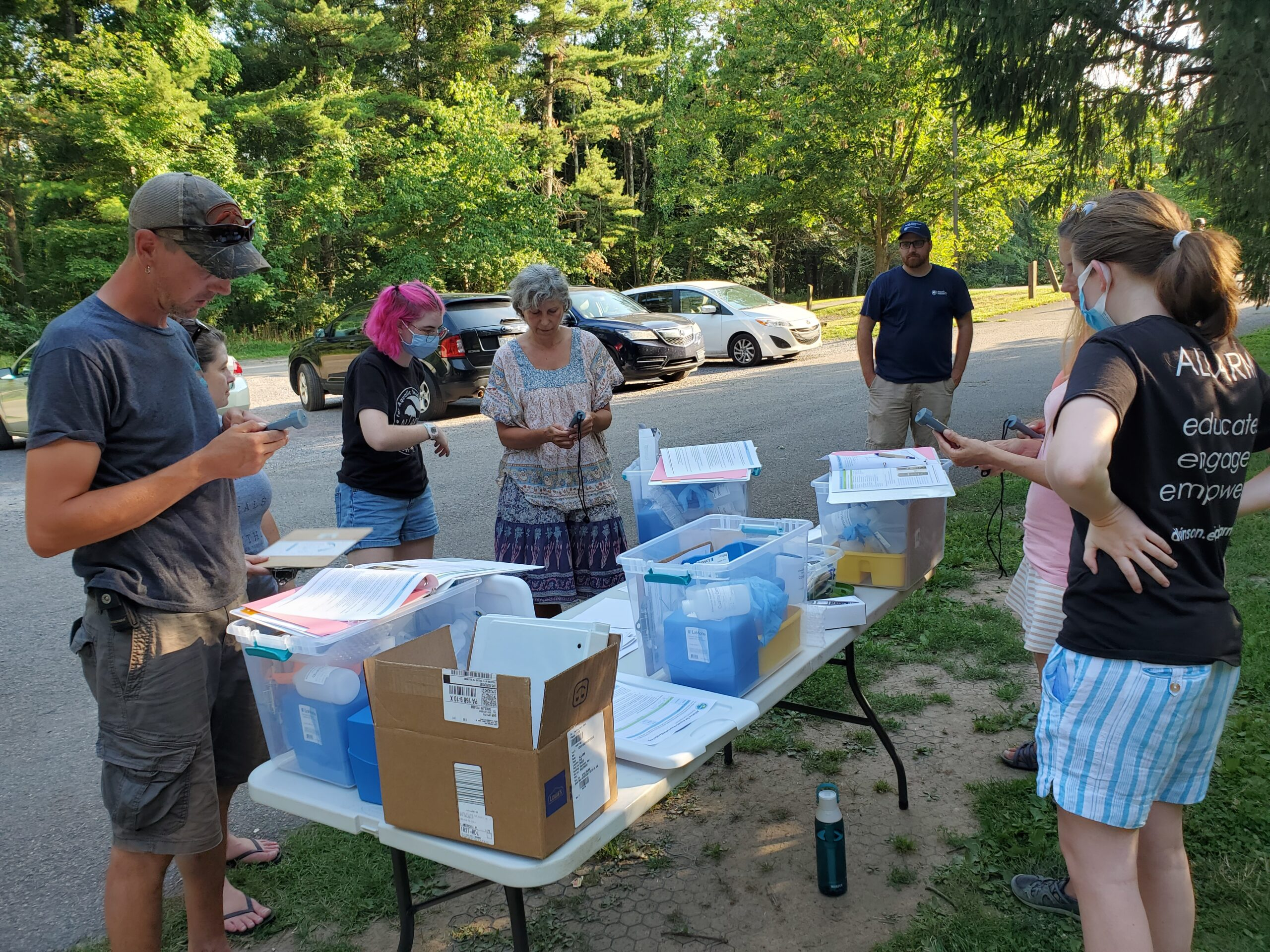 people stand around table with water quality monitoring equipment